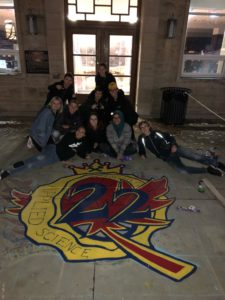 Sci '22 year executive team sitting in front of newly-painted Sci '22 year crest outside Clark Hall at night.